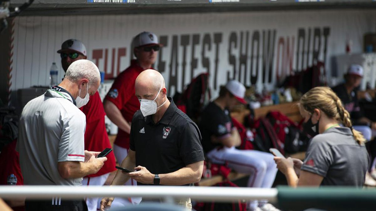 North Carolina State personnel chat in the dugout during a delay due to COVID-19 safety...