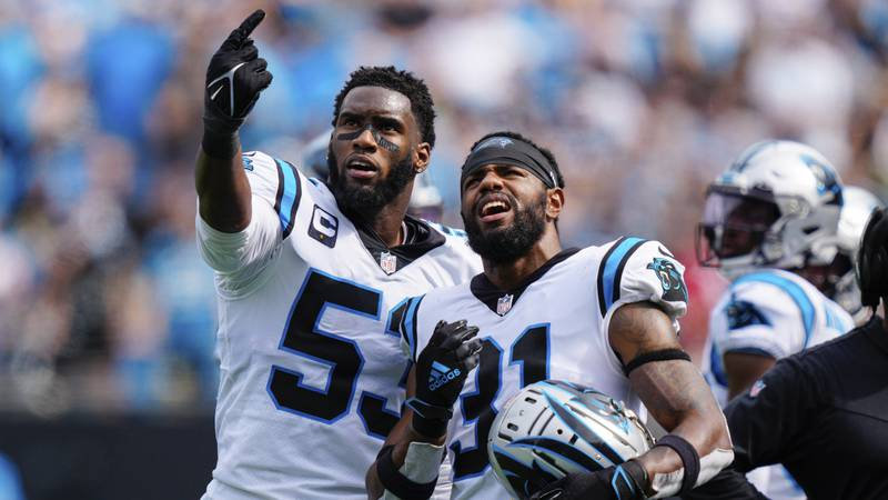 Carolina Panthers defensive end Brian Burns, left, and cornerback Juston Burris, right, watch a...