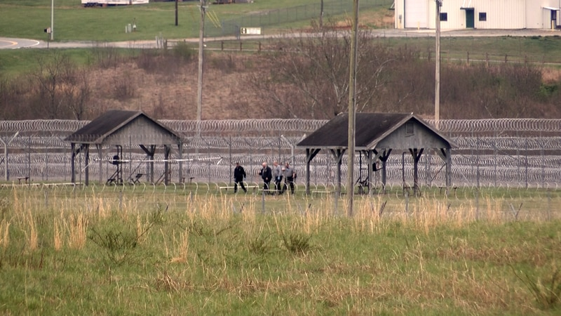 Staff and inmates walk behind the fence at Foothills CI.