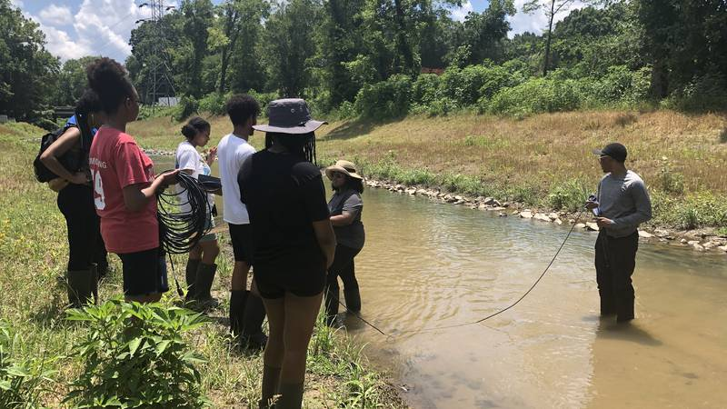 Students are collecting water quality samples in West Charlotte.