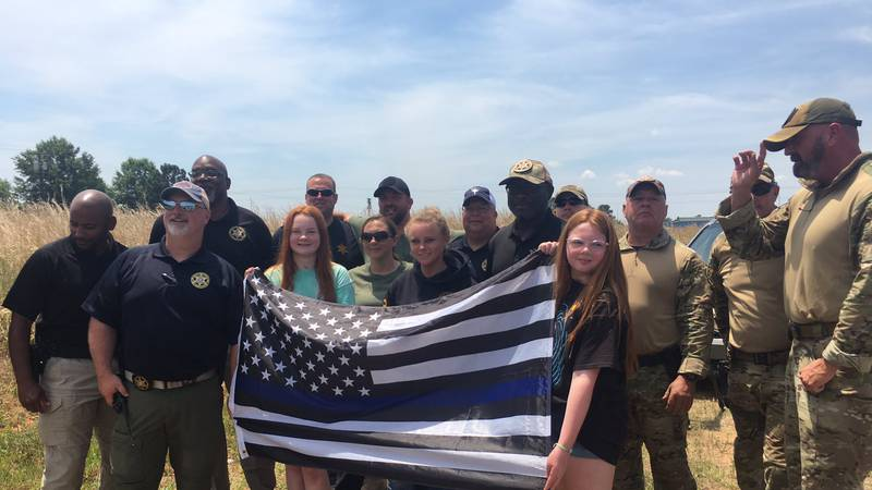 The Blankenship Family waved a police flag across from the law enforcement staging area after...