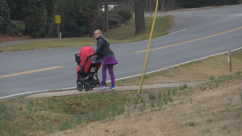A resident near Kuykendall Road in South Charlotte navigates the busy street with no sidewalk.