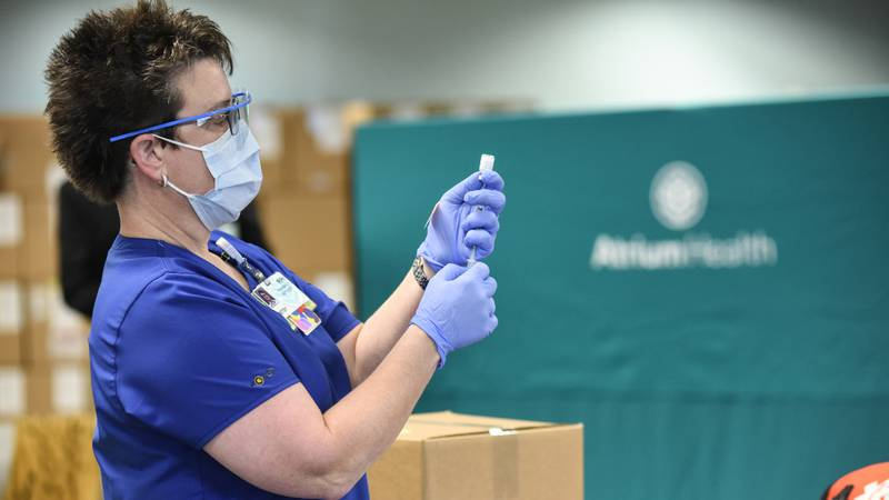 An Atrium Health employee prepares to administer the first dose of Pfizer's COVID-19 vaccine in...