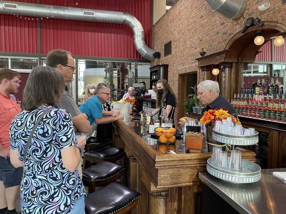 Customers buy liquor bottles at Southern Distilling Company on Sunday.