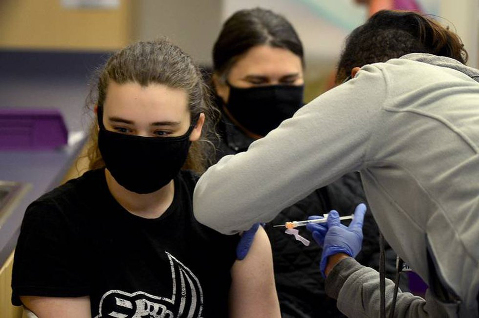 Elise Arnold, 15 years, left, receives her first COVID vaccination shot on Wednesday, May 12,...