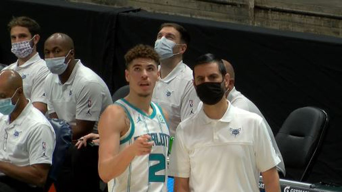 LaMelo Ball and James Borrego chat during Monday's NBA exhibition game between Charlotte and...