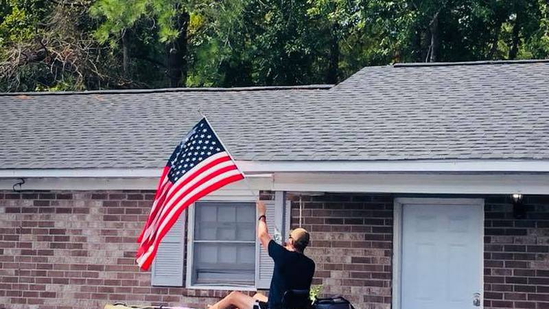 Todd Boehm fixing an American flag that was touching the water in Socastee. (SOURCE: Laura Boehm)
