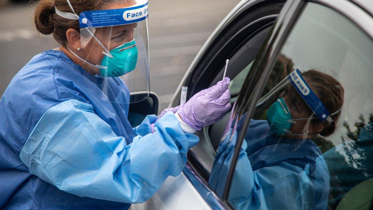 Kelly Mendenhall performs a coronavirus test at a drive-through testing site in Burlington...