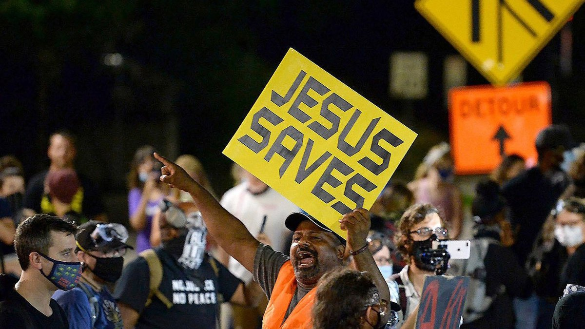 Sam Bethea encourages protesters with a word of faith during a protest in Charlotte, NC on...
