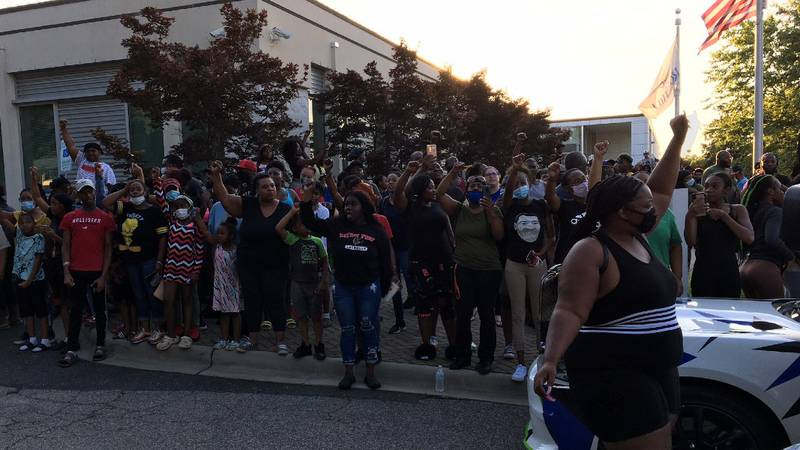 At least 100 people protested outside a police department in outrage over a Facebook video...