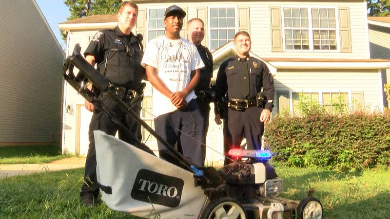 """Rodney Smith Jr. gets a little help from CMPD officers as part of his nation-wide """"Mowing with..."""