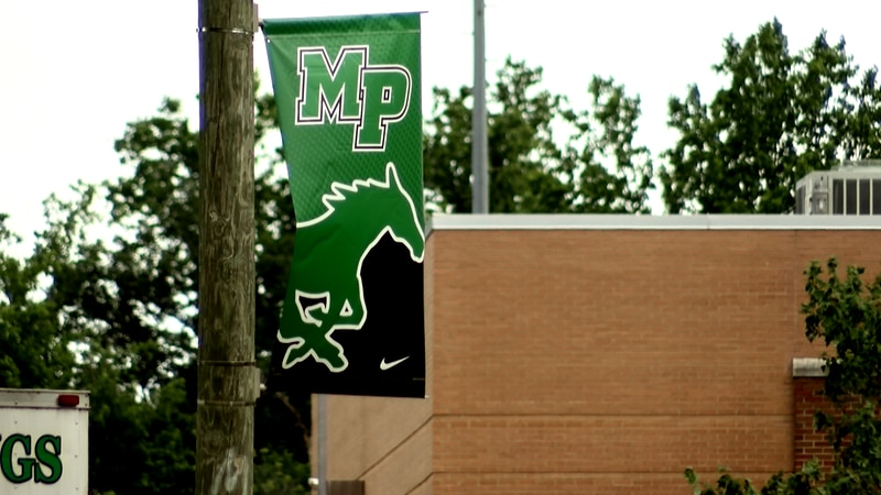 A banner hangs from a pole in the parking lot at Myers Park High School