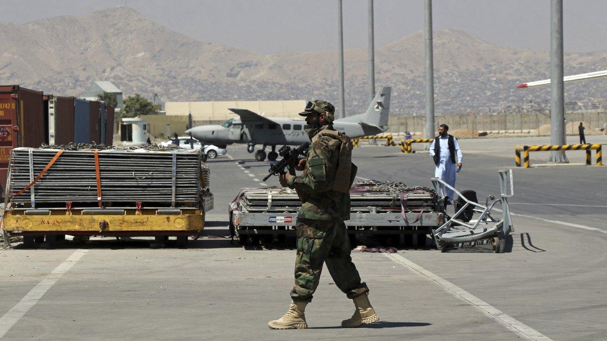 A Taliban soldier walks on the tarmac at Hamid Karzai International Airport in Kabul,...