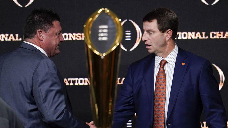LSU head coach Ed Orgeron, left, and Clemson head coach Dabo Swinney shake hands near the...