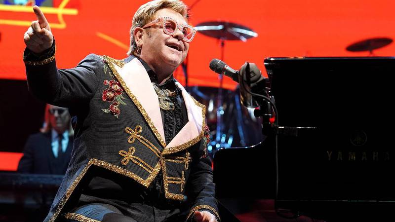 Elton John looks out at the audience and smiles while performing at Spectrum Center in...