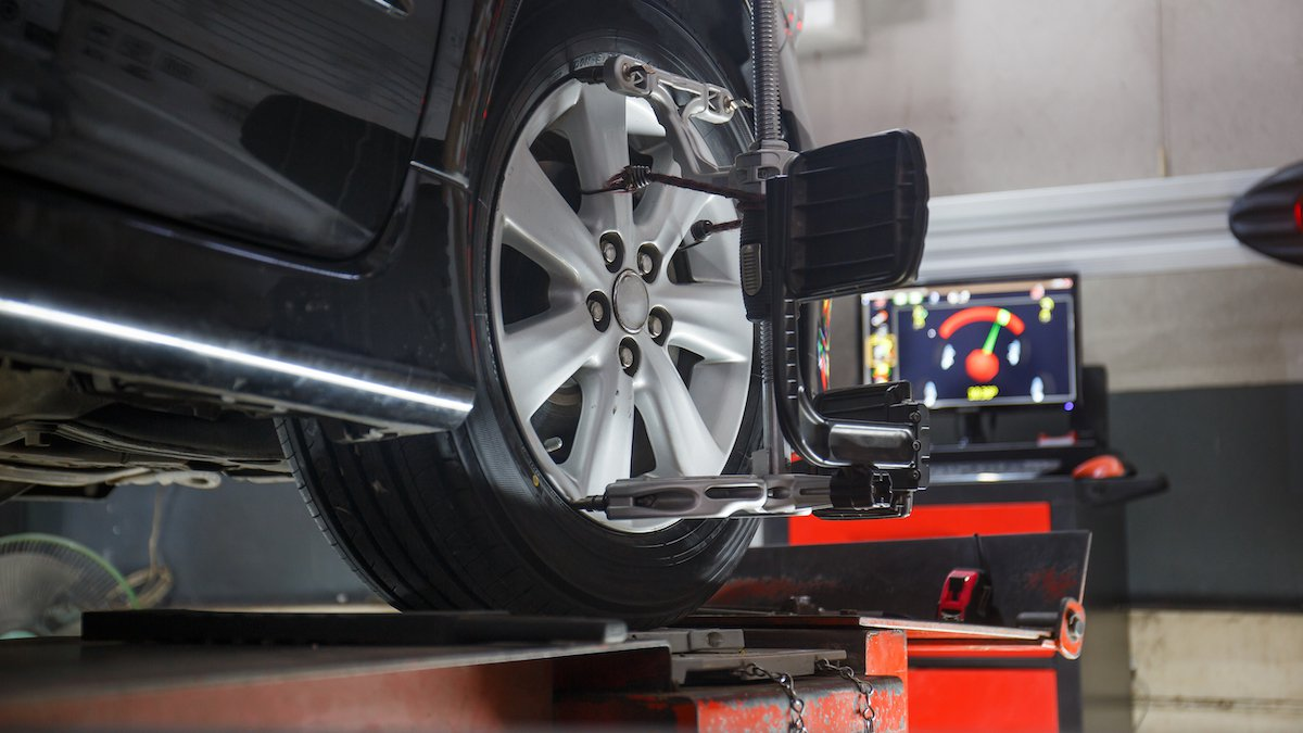 Car on stand with sensors on wheels for wheels alignment camber check in workshop of Service...