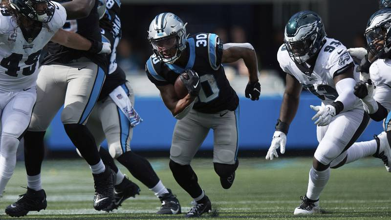Carolina Panthers running back Chuba Hubbard (30) runs through an opening in the line during an...
