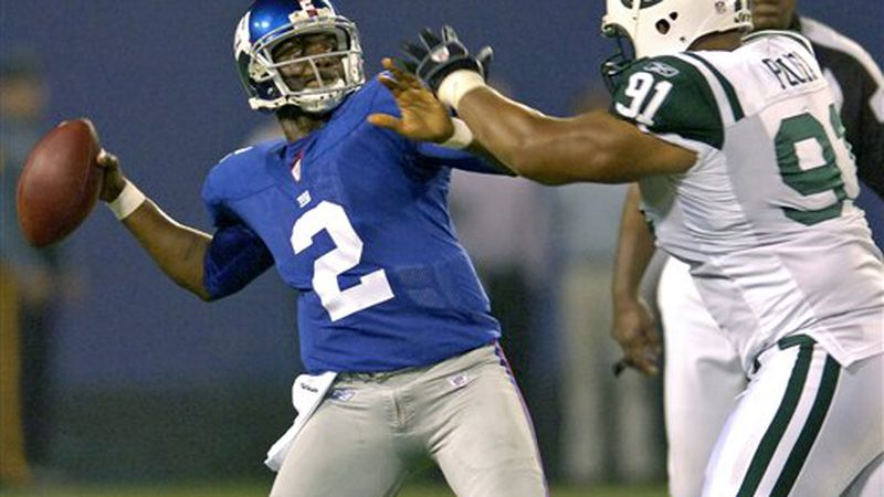 New York Giants quarterback Anthony Wright, left, looks for a receiver as he is pressured by...